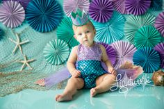 Mermaid 1st Birthday Cake Smash Photo and Props by Lightwork Photography, teal, turquoise, purple, lavender, seashells, fish netting, paper fans, rosettes, pinwheels, one year, outfit from ShopBelleThreads on etsy.com