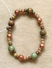 Learn How to Bead This Easy Netted Bezel! - 2. Materials:  •Cabochon (I used a 30x40mm oval gemstone cabochon for this tutorial, but it can easily be adjusted for any size or shape.) •2 grams size 11 seed bead in 2 contrasting colors (A, B) •20 3mm round copper glass Czech druk beads (C) •10 4mm gemstone beads in color to match or contrast cabochon (D) •Beading thread of your choice (6 lb. Fireline recommended)