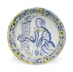 A DUTCH DELFT BLUE-DASH PORTRAIT CHARGER OF CATHERINE OF BRAGANZA  CIRCA 1685-1700  Painted in blue and yellow with a three-quarter length portrait of Charles II's consort standing by a speckled archway, a wreath in her hand, the border with a flower rinceau  15¾ in. (40 cm.) wide
