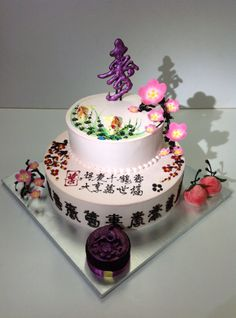 """- Chinese Birthday Cake with Cherry Blossom Chinese style Birthday cake with  3D Cherry flower in chocolate  Chocolate """"Shu"""" plaque meaning Logevity Chocolate lace in ancient chinese around cake  A pair of longevity peaches signifying eternity A pair of chocolate carps Carved chocolate crane cake in metallic fuschia"""