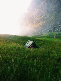 beautiful tent camping in the middle of a wild field with fog coming in.