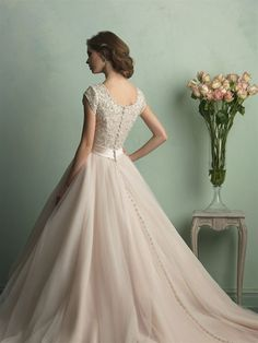 This regal gown features a ballgown skirt and intricate beading throughout the bodice.