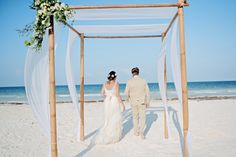 Jimmy & Claire's destination wedding : A bamboo canopy covered with a white sheet and decorated by a white and green bouquet of eucalyptus, white roses and some greenery - Venue : Casa Maya Kaan - Decoration : Aquadeco - Flowers : Xochitl Botanicals