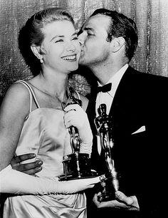 Grace Kelly gets a smooch from fellow Academy Award winner, Marlon Brando, at the Oscars, March 1955.