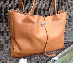 Simple and sleek design, Hand-made by Charezza Leather  This shoulder bag is made of Nice cognac-coloured leather. Size is 30 x 39 x 9 cm, there applies a A4 in and a macbook 13   At the bag fits a inner pocket with zip also known as clutch to use. On the inside of the bag you can pin this clutch, so are your precious belongings safe. This inner pocket/clutch is loose.  On the outside of the bag shows off a beautiful edelweiss. These do you use as closure.  For each bag I use a new piece...