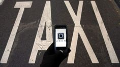 Uber app and a taxi sign on the ground