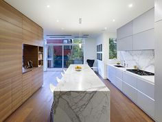 """""""The walnut unit between the kitchen and dining room ties into the fumed oak floor,"""" Dubbeldam says. """"The rest of the materials in the house—glass, marble, stone—were selected to offset the wood. Kitchen Designs Photos, Kitchen Photos, Modern Kitchen Design, Toronto Houses, Bathroom Photos, Kitchen Dining, Dining Room, Kitchen Wood, Kitchen Tips"""