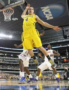 Michigans Mitch McGary takes a hard hit from Floridas Patric Young in the first half in the NCAA Tournament,