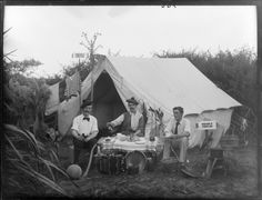 Tam o' Shanter and tea, with piano accordion, pots and pans, basketball and stove in front, tent with clothing drying and 'Thistle' camp sign. Photographer: Maclay, Adam Henry Pearson, 1873-1955.