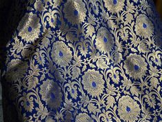 Silk Brocade Fabric in Blue Gold Weaving, Banaras Brocade Fabric. This is a beautiful pure heavy banaras silk brocade floral design fabric in Blue and Gold. The fabric illustrate golden woven...