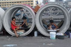 A woman (R) washes laundry as two girls do their nails in culvert sections used as shelters in Manila, Philippines