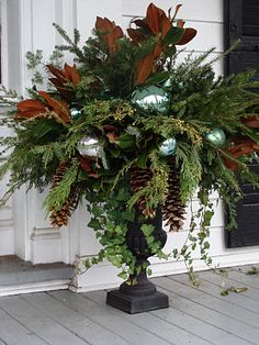Holiday design for outdoor urn or pot using pine cones, fir branches, other branches that one has around that eill last in Fall / Winter and colored bulbs of your choice. from blog Black-eyed Susan: