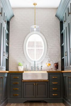 Farrow and Ball Downpipe butlers pantry cabinet with brass hardware and brass lighting. Caitlin Creer Interiors. C. S. Cabinetry & Design