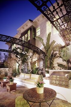 Tropical Patio with Tropical garden, Arbor, Built-in bench seating, Tile table top, exterior stone floors, Trellis, Fence