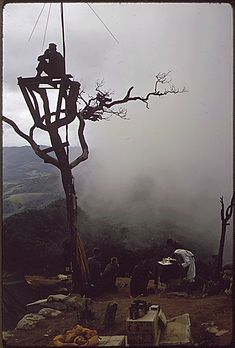 Vietnam….A Marine stands watch in an observation tower as Lieutenant Commander McElroy, the 3rd Battalion, 26th Marines chaplain, holds mass on Hill 950., 07/31/1967
