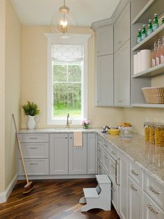 Gray pantry features gray cabinets paired with gray granite countertops placed under stacked open shelving.