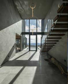The staircase and entrance are part of a double-height volume with large windows Build A Fireplace, Fireplace Wall, Sunken Living Room, Open Staircase, Black Exterior, Environmental Design, Large Windows, Skiing, Entrance