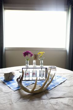 Simple centerpiece with glass milk jug and blue gingham paper