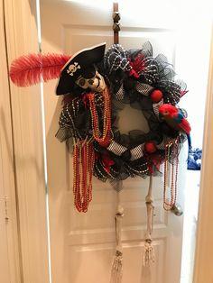 Gasparilla Wreath with Pirate Skeleton, Parrot, and Red/Gold Beads! Skelton wreath, pirate Wreath, H Pirate Skeleton, Pirate Halloween, Pirate Party, Halloween Ideas, Halloween Mesh Wreaths, Christmas Wreaths, Pirate Wreath, Pirate Decor, Dollar Tree Crafts