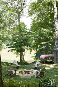 Adirondack chairs encircle a fire pit made of large-slab Crab Orchard stone and native river stone; his and her canoes are nearby. Landscape Design, Garden Design, House Yard, Cottage Exterior, Cottage In The Woods, Atlanta Homes, River House, Maine House, Outdoor Living