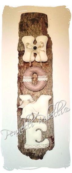Scritta realizzata in feltro imbottito, con l'aggiunta di pizzi e nastri, su corteccia naturale