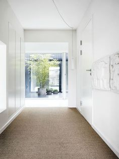 Villa Weinberg, Aarhus, Denmark, White Hallway with sisal jute carpet, potted bamboo plant in concrete planter | Remodelista
