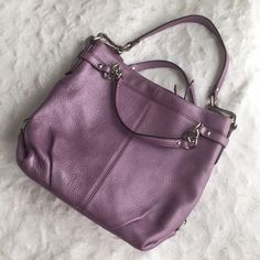 "Coach Leather Brooke Hobo F17165 Authentic Coach purse made of soft pebble leather in lavender. Two handles with a drop of approximately 3"" to the top of the purse, and a single handle with a drop of approximately 8"" to the top of the purse. Zip closure. Inside is fully lined. Two accessory pockets and one zippered pocket. Purse measures approximately 14"" wide x 11"" high x 4"" deep. Has one leather hangtag. Outside has minimal signs of wear, if any at all. Inside has a few makeup/pen stains…"