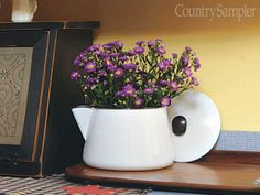 Plop a potted plant inside an enamelware coffee pot or bean pot with a wide opening. This is a great way to repurpose a pot with a missing lid. To prevent water damage, set a plastic tray inside before placing the plant inside.