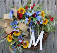 Sunflower Wreath  This wreath is the perfect personalized accent for spring and summer. A wired burlap ribbon makes a wild bow. Beautiful, realistic golden sunflowers, sweet peas, wild roses and fern surround the bow. This wreaths fern and blooms have a light and airy feel where the grapevine base is visible in places. A white monogram letter of your choice adds a personal touch. Average diameter:21 This wreath is made on a grapevine base measuring approximately 18  Indoor/ Sheltered Out...