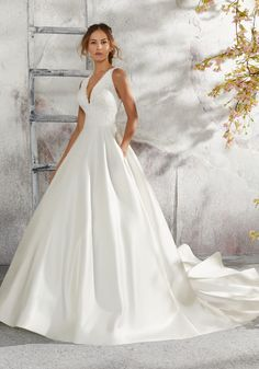 This elegant sleeveless Laurie designer bridal gown features beautiful appliquès, lace, and beading on an intricately designed satin wedding dress. The v-neck neckline completes the ball gown silhouette of this designer bridal gown. Wedding Dress With Pockets, V Neck Wedding Dress, Classic Wedding Dress, Perfect Wedding Dress, Western Wedding Dresses, Wedding Dresses Photos, Bridal Wedding Dresses, Dream Wedding Dresses, Mori Lee Wedding Dress