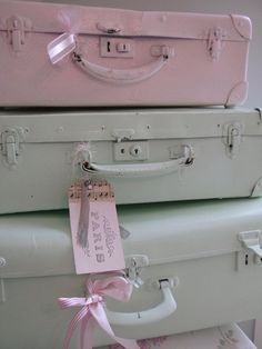 .Painted pink and seafoam green suitcases.