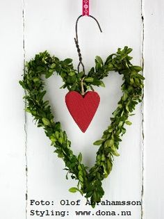 Christmas wreath made by bending a wire hanger into a heart, and decorating it with greenery and a heart ornament