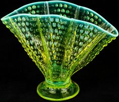 """Lot 43 in the 2.2.16 online & live auction! An awesome vintage opalescent, topaz yellow, uranium glass vase. It is fan shaped and features a pleated handkerchief design with a hobnail conical dot pattern. It glows bright green when placed under ultraviolet light. It is unmarked but appears to be Fenton Art Glass. Measures 8"""" tall x 10.75"""" wide. #Decor #Collect #Home #POGAuctions"""