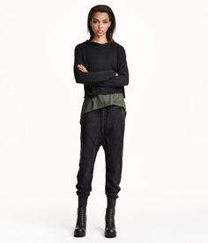 Sweatpants with dropped gusset and tapered legs. Elasticized drawstring waistband, side pockets with zip, and one back pocket. Ribbed cuffs.