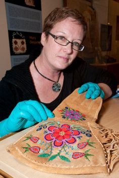 Curator Joanne White examines a beaded men's gauntlet at the Musée Héritage Museum. The glove is one of about 30 items in the exhibit on Mét...