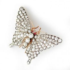 A Victorian diamond butterfly brooch, the body and wings encrusted with round old brilliant-cut diamonds, estimated to weigh a total of 11 carats, set in silver to a yellow gold backing, with cabochon-cut ruby eyes, circa 1840