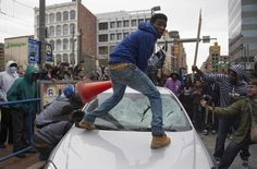 Demonstrators destroy the windshield of a Baltimore Police car as they protest the death Freddie Gray. (Photo via Jim Watson/Getty Images)
