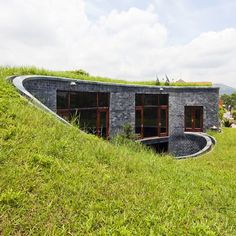 Spiralling stone house in Vietnam by Vo Trong Nghia with grass on its roof and an oval courtyard at its centre.