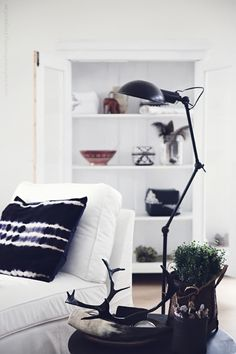 living room with white chair, tie dye throw pillow, black arm lamp & antlers #homedecor #interiordesign
