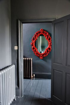 Great red mirror against dark interior. Old Radiators, Grey Hallway, Dark House, Red Mirror, Pin On, Gothic House, House Entrance, Red Interiors, Red Accents
