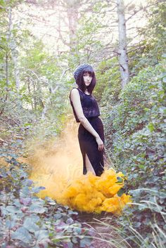 Woman with yellow smoke bomb