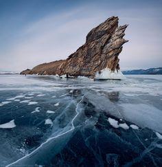 Rock in the cracked ice of Lake Baikal, Siberia