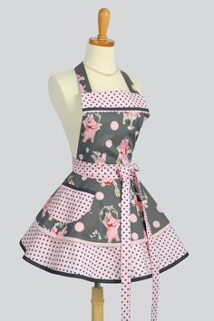 Cute and sassy ruffle apron is full of whimsical pink elephants sipping and having fun in Michael Millers Its A Girl Thing fabric. Pink and white dumb dots for trim and underskirt make the apron a fabulous apron for serving or just wearing at home. Quality fabrics, fully lined bodice, waistband, pockets that are a trademark of Creative Chics. Tie in front or tied in back you will look super cute day after day in this modern retro apron styling.    (Petticoat not included.)    All seams are…