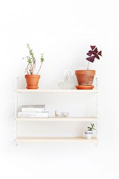 When styling accessories, to create the most visually pleasing arrangements, place items in groups of odd numbers like the pots seen on this top shelf. Designers know that objects by themselves or grouped in threes create harmony in a composition. If you have several small items, choose five to display as a collection to make a strong statement
