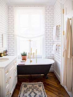Natural wood and terra-cotta accents warm up the bathroom's cool palette.