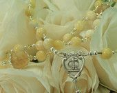 Yellow Bridal Rosary •	Decade beads warm Semi-Precious Champagne Yellow Jade Gemstones (8mm) •	Our Father beads gorgeous (12mm) Semi-Precious Citrine Gemstones accented capped with silver petal caps •	Sterling Silver and Swarovski Xillion Cut Jonquil Crystals beautifully sprinkled throughout compliment the beauty of this piece •	This Piece is shown with the stunning Wedding Intertwined Circles Sterling Silver Crucifix and Center