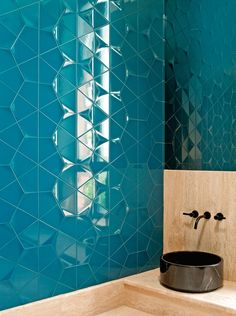 Designer Christopher Hall has created an unusual feel in this bathroom with high gloss hexagonal blue tiling