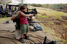 Muller Sony Awards People_05 by Pete Muller   •     A young boy is supported as he fires a fully automatic machine gun. Safety regulations at OFASTS( Oklahoma Full Auto Shoot and Trade Show) are extremely tight with all shooters carefully monitored by exhibitors.