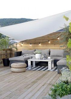 un jardin terrasse doté d'une guirlande lumineuse d'un salon de jardin et d'une voile protégeant du soleil