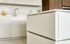 Modern walnut and white kitchen in Wimbledon featuring: split level island, integrated appliances, breakfast cupboard and sleek handle-less kitchen storage.
